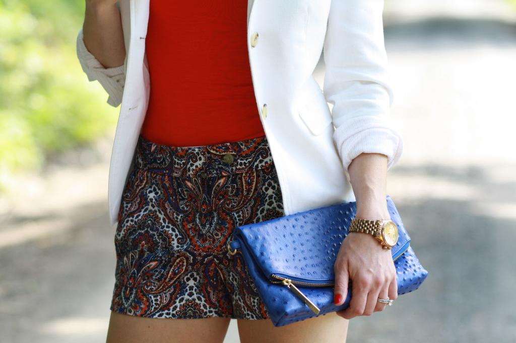 white blazer rolled sleeves, orange top, paisley shorts, cobalt blue Brahmin Duxbury clutch