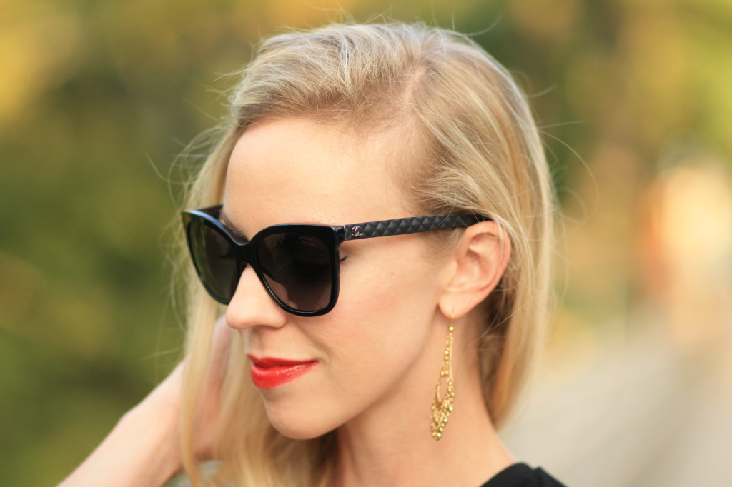 black oversize Chanel sunglasses with leather trim, red lip, gold chandelier earrings, Bare Minerals Live it Up lipstick