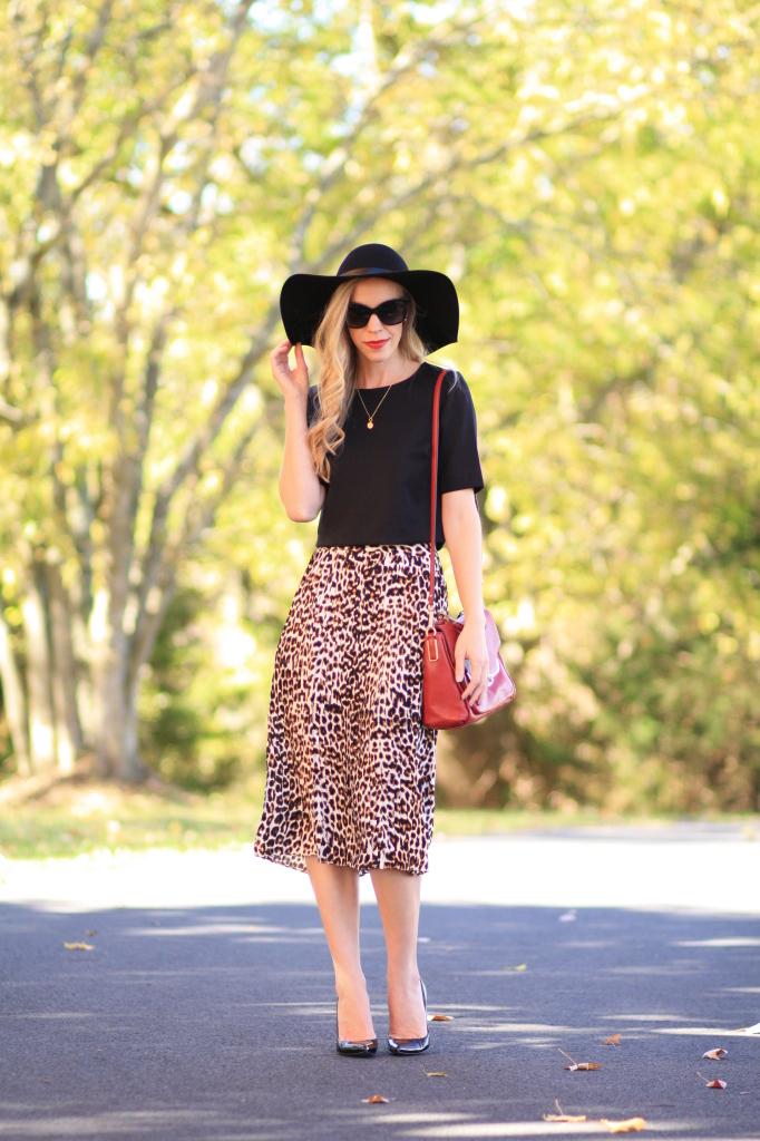 black floppy wool hat, black crop top, Express leopard print midi skirt, Stuart Weitzman black patent Nouveau pump, Chanel cateye sunglasses, red Coach leather bag, red black and leopard outfit