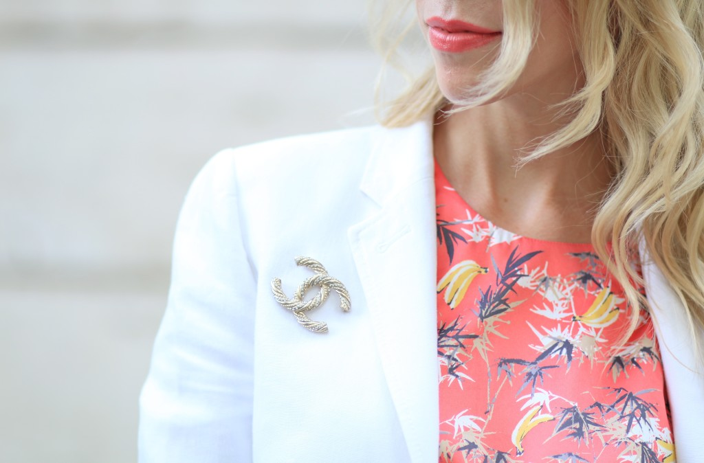 Estee Lauder Surreal Sun coral lipstick, tropical print silk romper, white blazer with gold Chanel brooch
