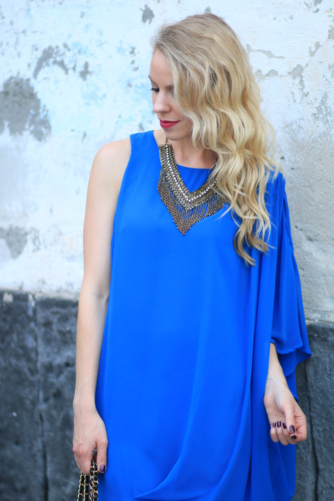gold statement necklace with solid color dress, cobalt blue one shoulder flowy Grecian style dress