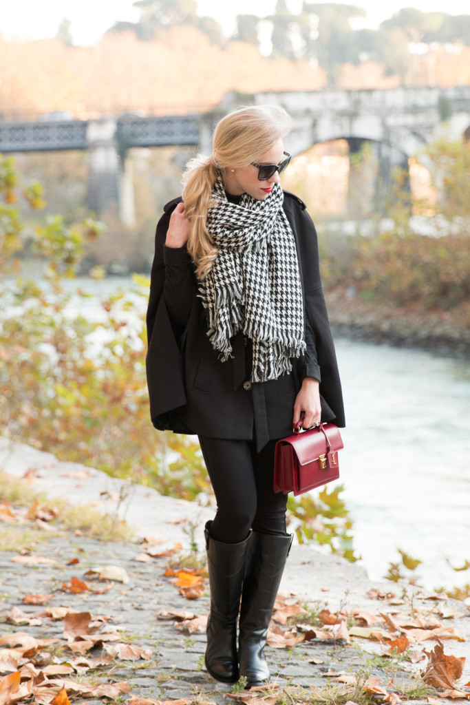 black cape with black riding boots and houndstooth scarf, houndstooth scarf holiday outfit, red YSL High School bag, Frye Melissa Tab Tall riding boots
