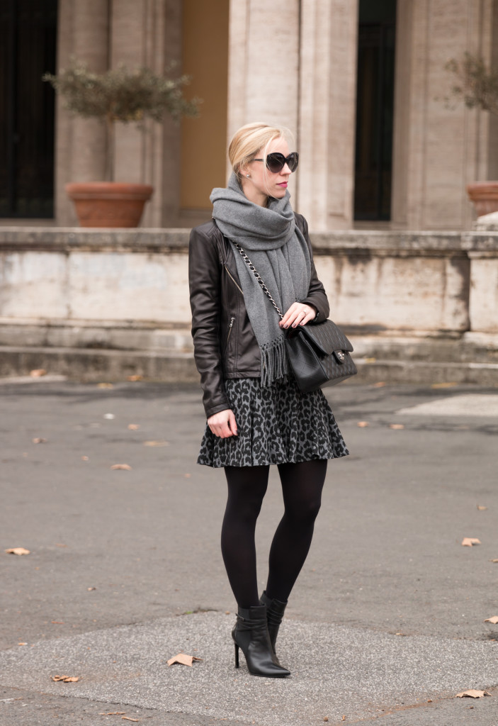black leather moto jacket with gray oversized scarf and leopard skirt, how to layer a leather moto jacket for winter, flounce mini skirt with tights and booties