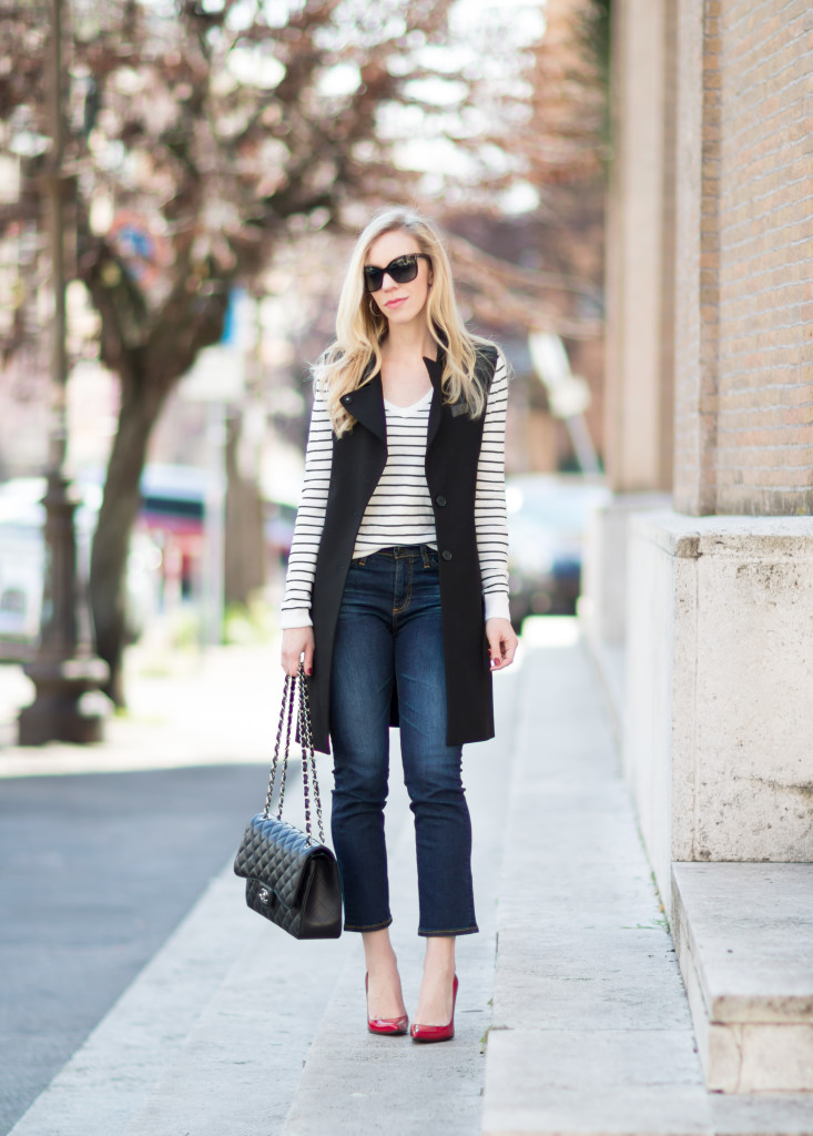 black and white striped sweater with long black vest, crop flare jeans with pumps, how to wear crop flare jeans, long black vest outfit
