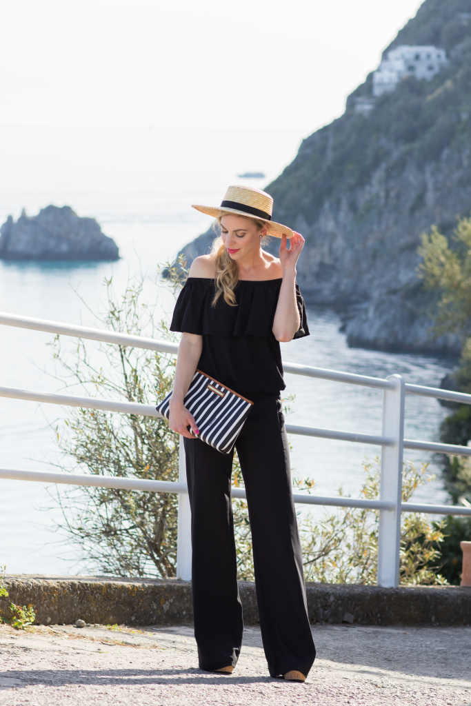 black off the shoulder blouse with wide leg pants, black and white striped clutch, straw boater hat summer outfit