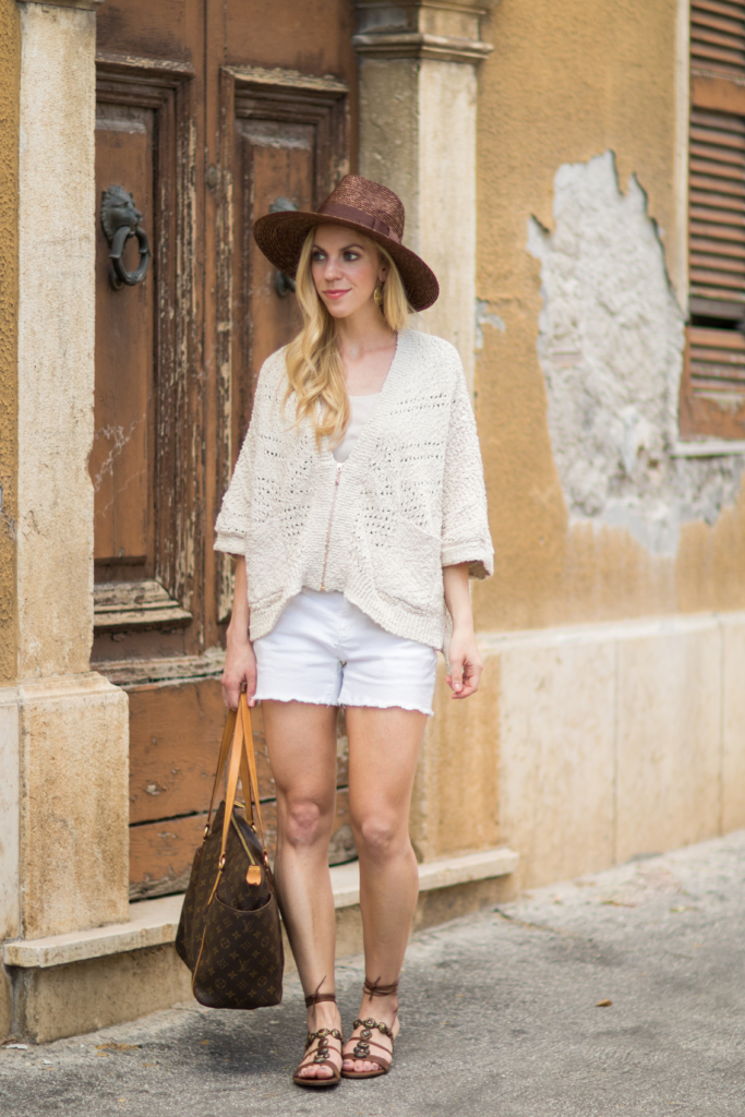 beige poncho with white denim cutoff shorts, Stuart Weitzman 'Stoned' lace-up sandals, neutral summer outfit with beige and white, summer poncho outfit