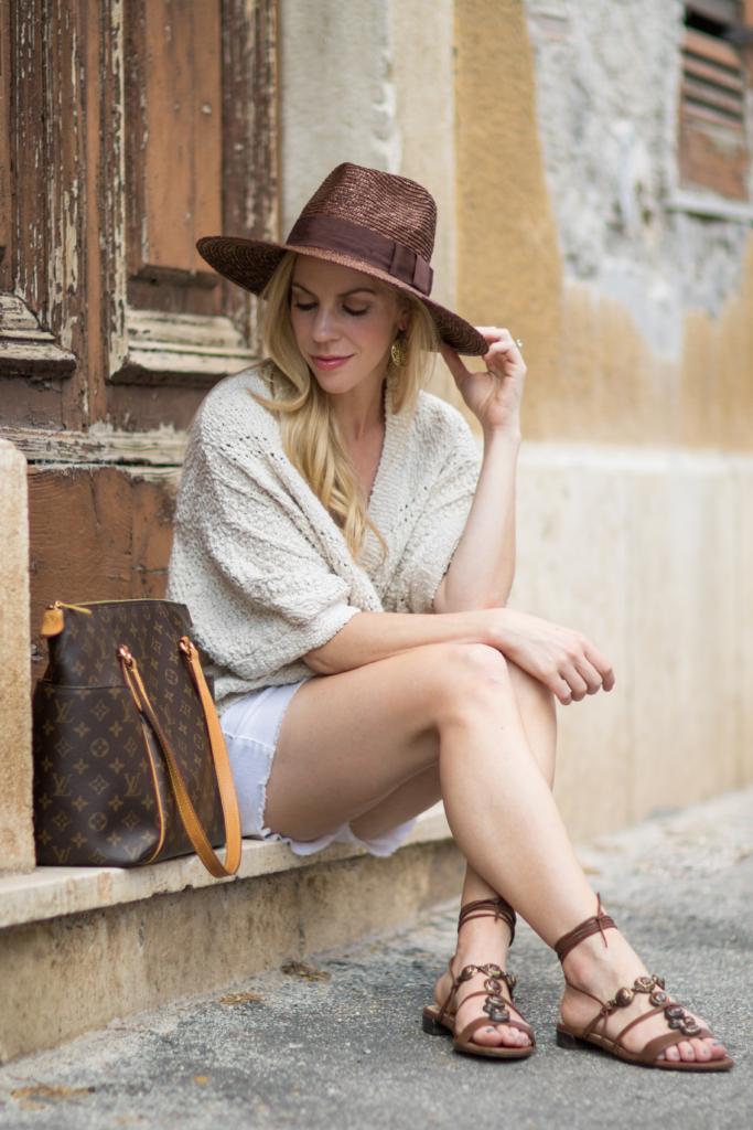 neutral summer outfit with beige sweater and white denim shorts, Stuart Weitzman 'Stoned' lace up sandals, Brixton 'Joanna' brown panama hat