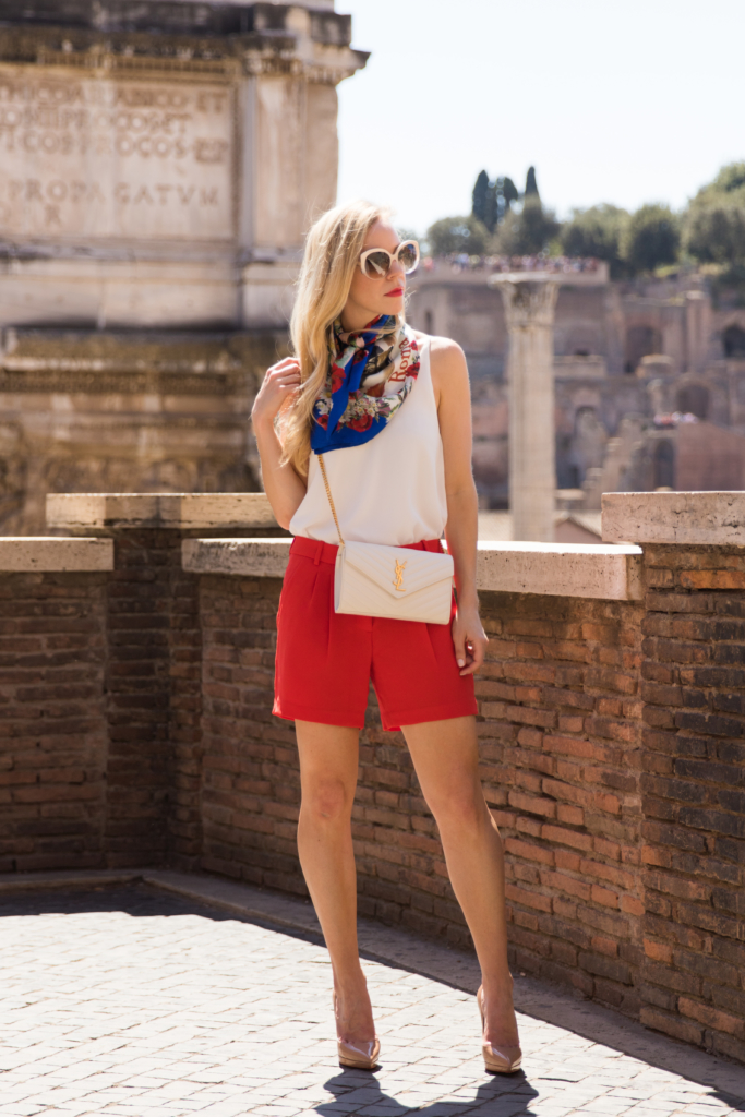 Dolce & Gabbana silk scarf Postcards from Italy, bright red pleated shorts with nude pumps, Saint Laurent white matelasse chain wallet, Christian Louboutin nude pigalle pumps