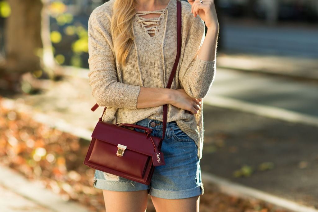 Saint Laurent High School satchel oxblood red, lace-up sweater with distressed denim shorts