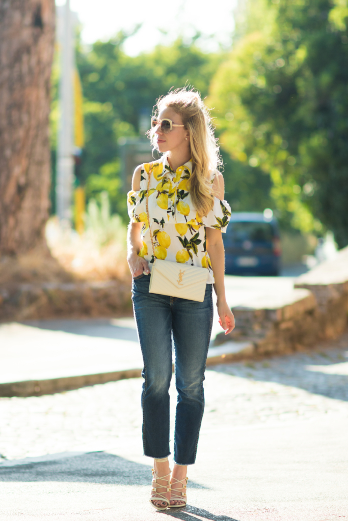 cold shoulder lemon print top, 7 for all mankind high waist raw hem jeans, Saint Laurent white chain wallet, Valentino white Rockstud sandals
