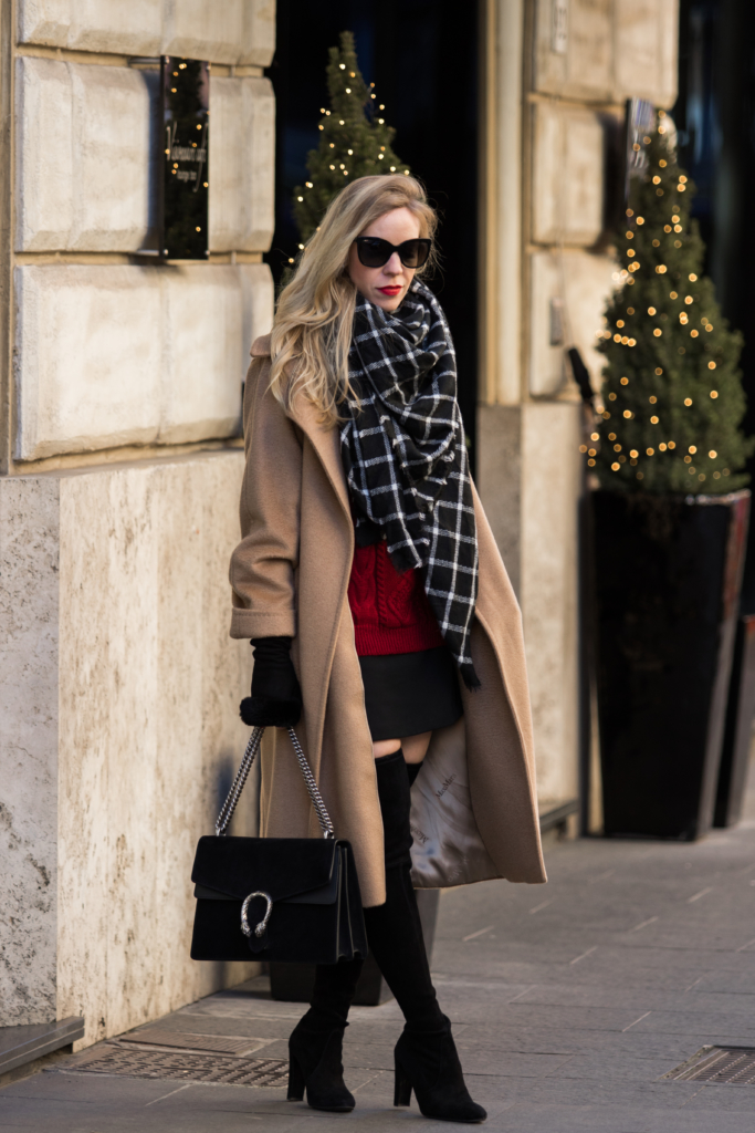 max-mara-camel-coat-with-red-sweater-and-black-mini-skirt-black-and-white-windowpane-blanket-scarf-camel-coat-with-black-and-red-holiday-outfit