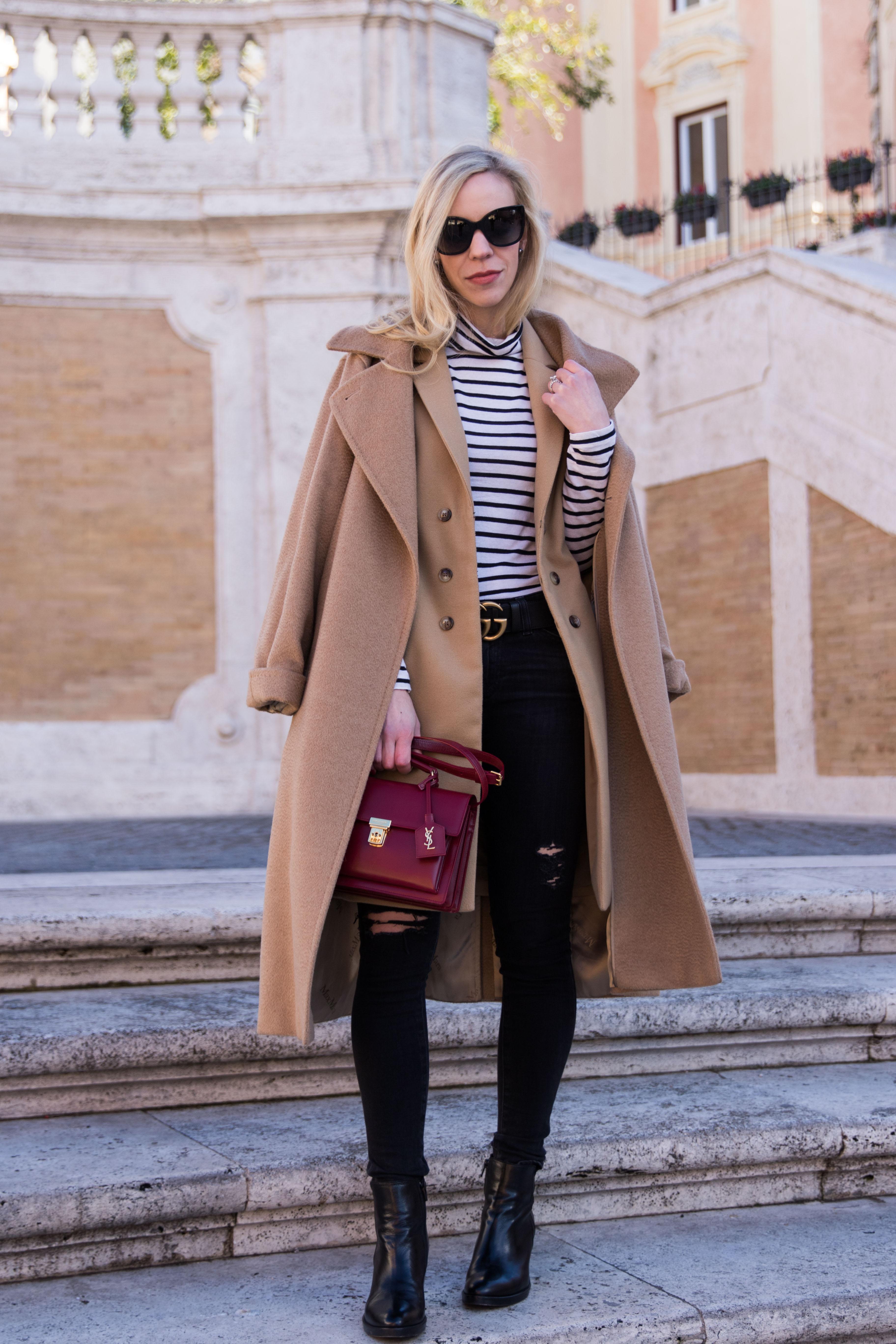 fashion blogger Meagan Brandon wearing Max Mara Manuela camel coat with striped turtleneck and black jeans, Saint Laurent red High School bag