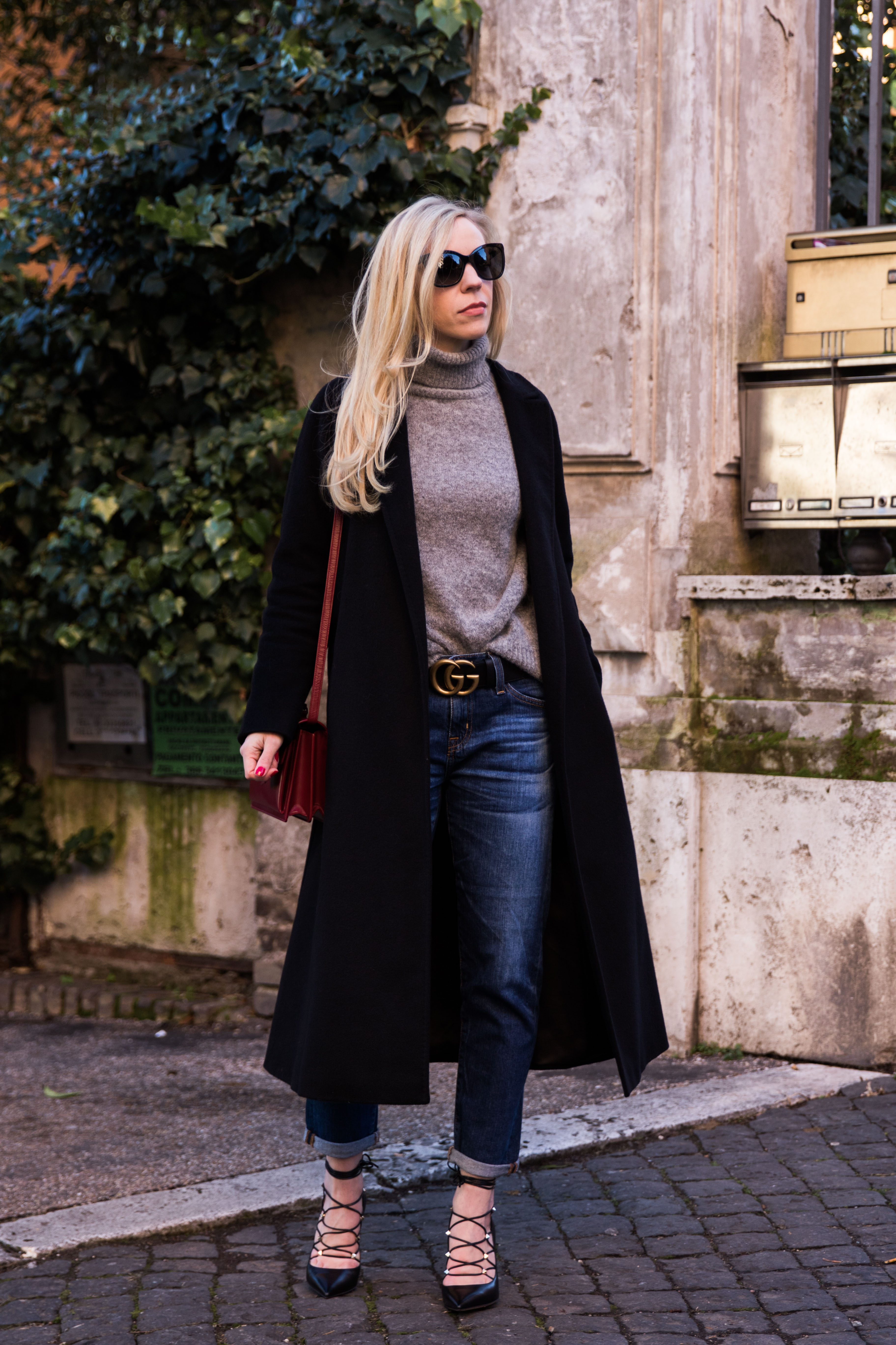 fashion blogger Meagan Brandon wearing Max Mara black wrap coat with turtleneck, Gucci belt and boyfriend jeans, Valentino lace-up pump