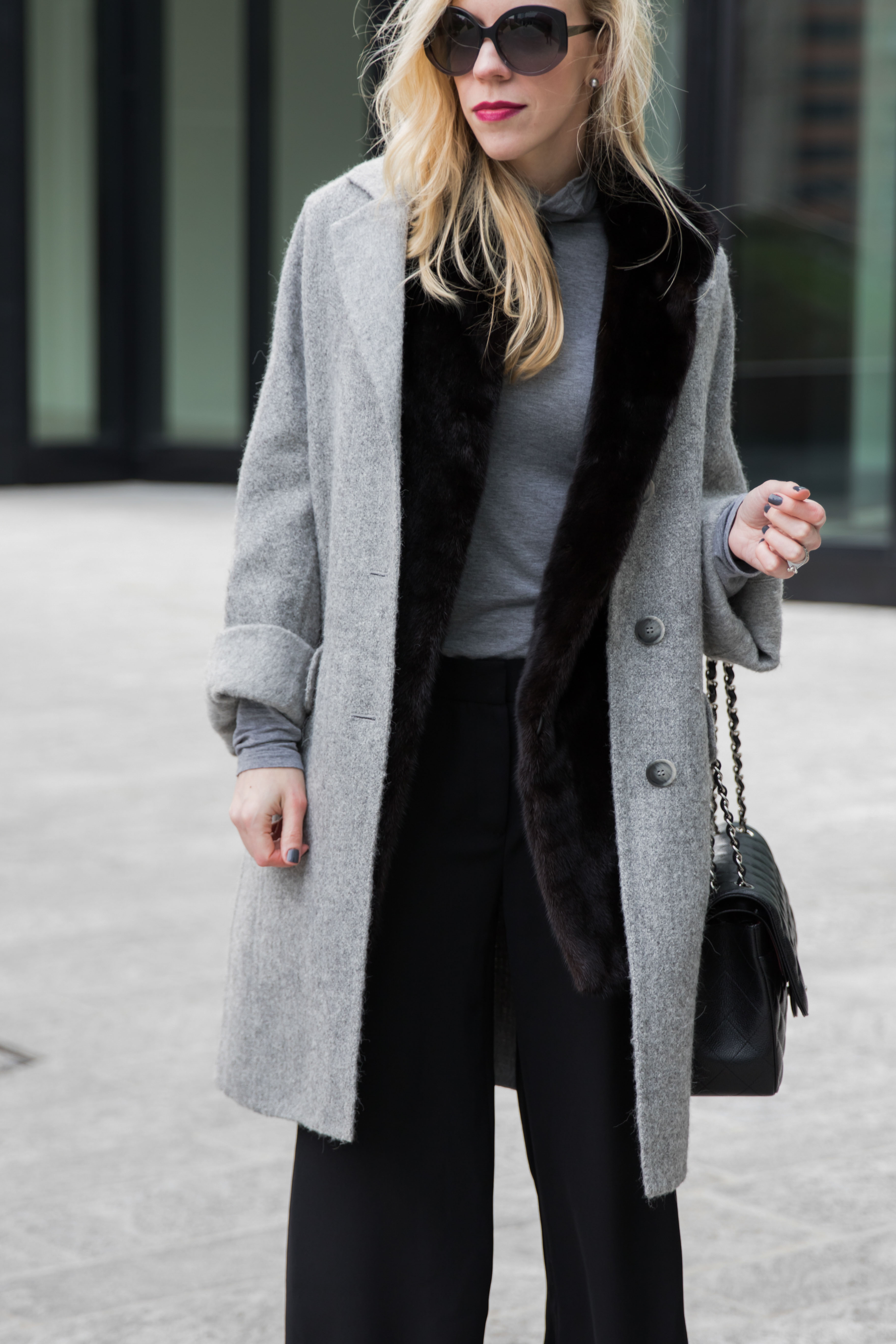 oversized gray coat layered over fur vest, Dior oversized Extase sunglasses, NARS Scarlett Empress berry lipstick