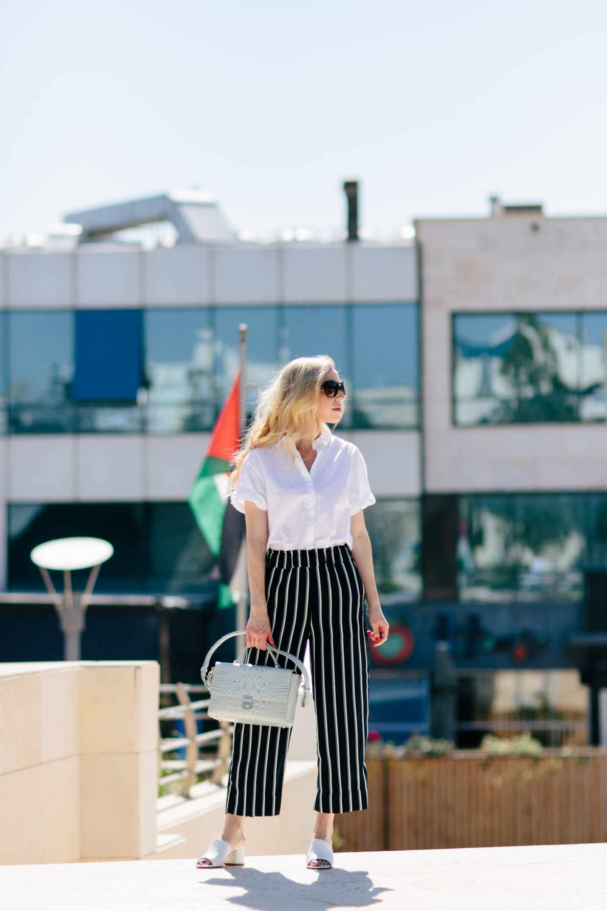 5ac17b0c5b Meagan Brandon fashion blogger in Amman, Jordan wearing white shirt with  striped wide leg culottes and white mules, how to wear striped pants for  summer