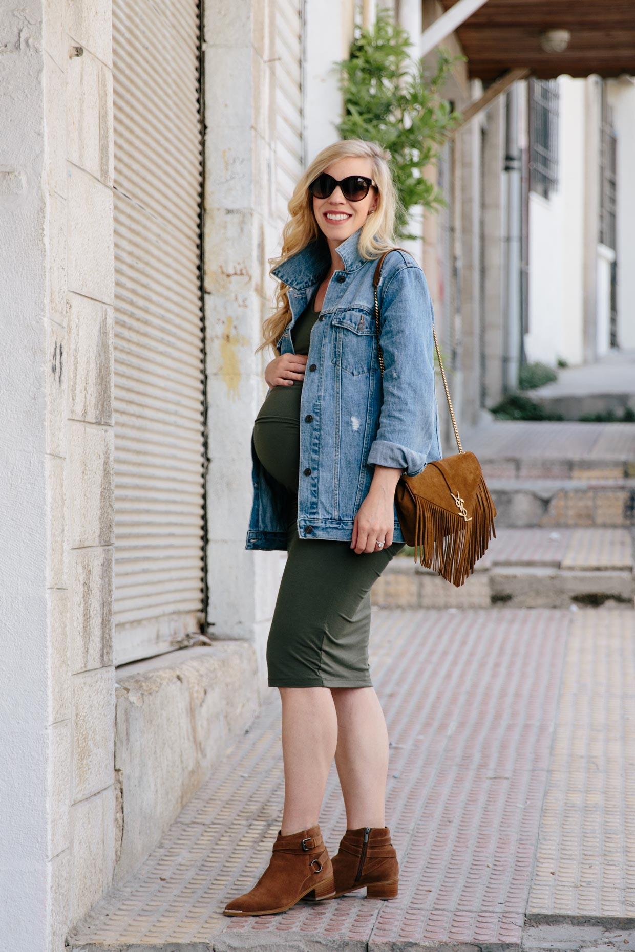 a8f4a94c56ec2 Meagan Brandon fashion blogger of Meagan's Moda wears oversized denim  jacket with olive ruched maternity dress and western suede ankle boots 34  weeks ...