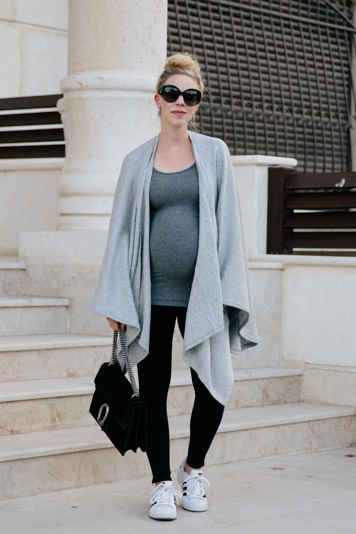 9cd9492194d0a Meagan Brandon fashion blogger wears comfy and chic maternity travel outfit  with Ingrid & Isabel leggings, nursing wrap poncho and Adidas Superstar  sneakers