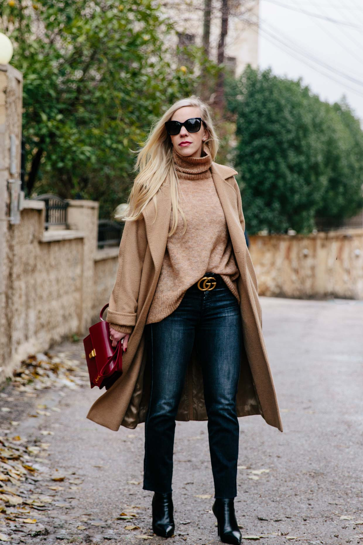 f3bbe5c2ce0 Meagan Brandon of Meagan s Moda fashion blog shows how to wear a classic  camel wrap coat with straight leg denim and Gucci belt