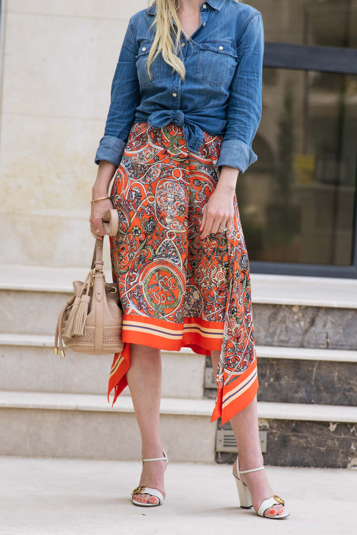 95403f8e3 Summer outfit idea with denim shirt tied at the waist, printed silk skirt  and Gucci block heel sandals