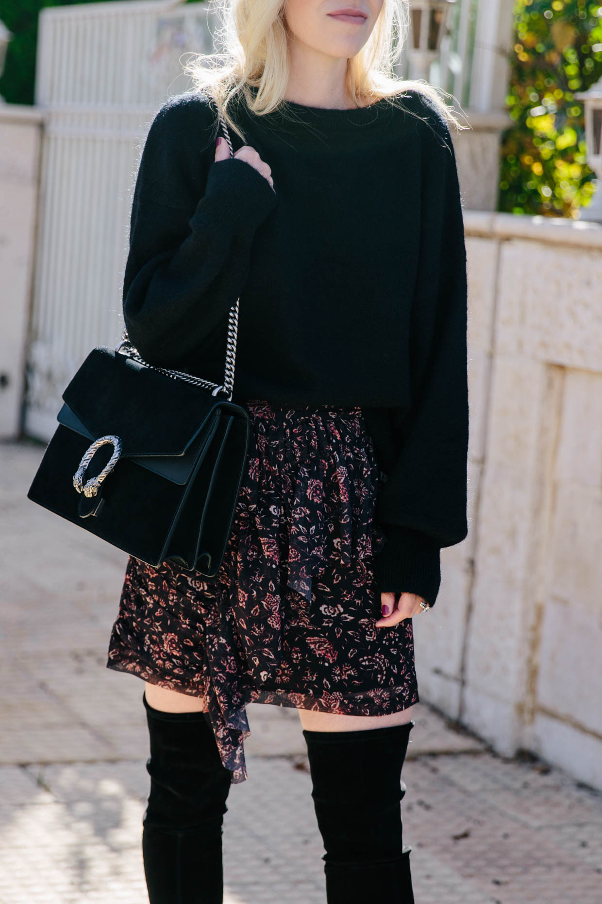 32c61ed0075 Meagan Brandon fashion blogger of Meagan s Moda wears oversized black  sweater with floral ruffle mini skirt and suede over the knee boots for  fall