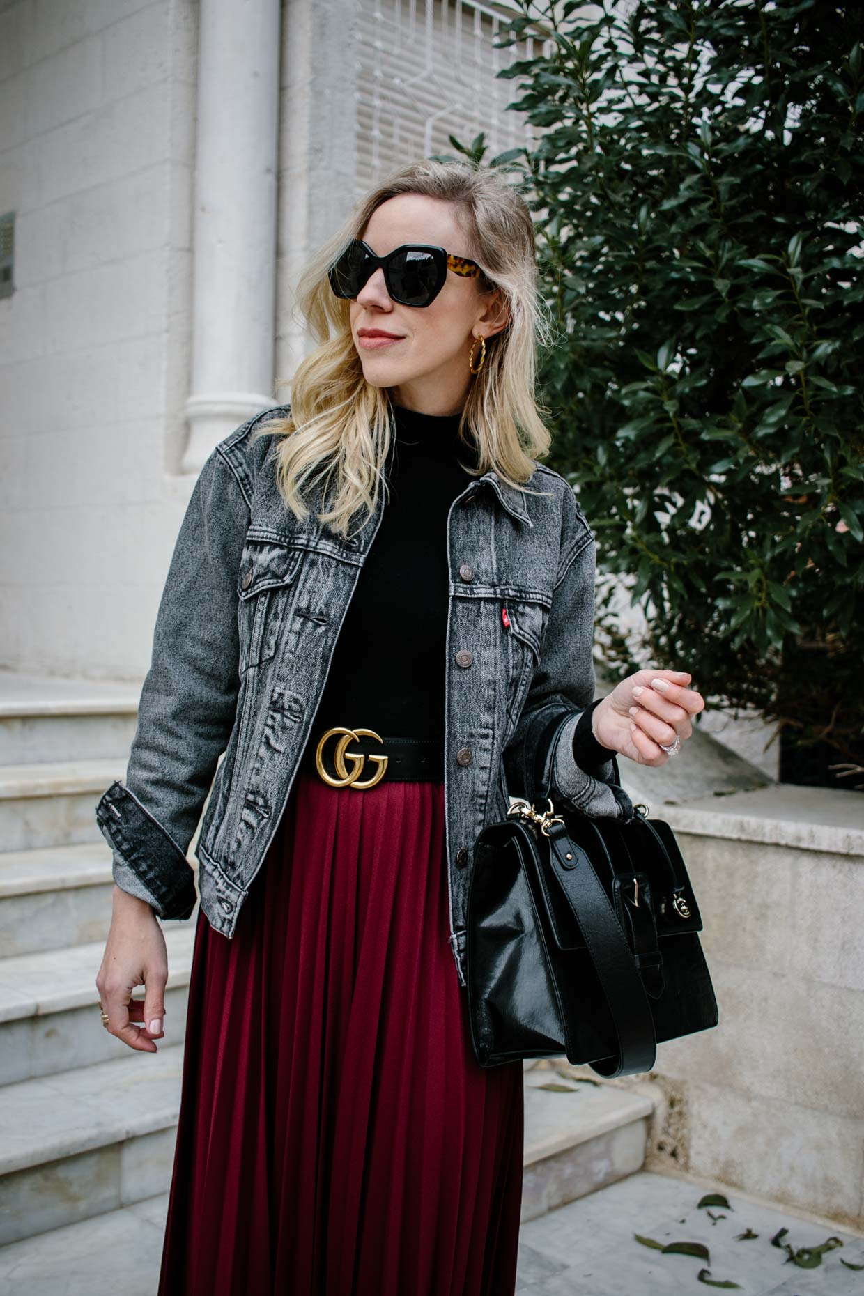 Meagan Brandon fashion blogger of Meagan's Moda styles Levi's black denim trucker jacket with Gucci belt, burgundy pleated skirt and black bodysuit