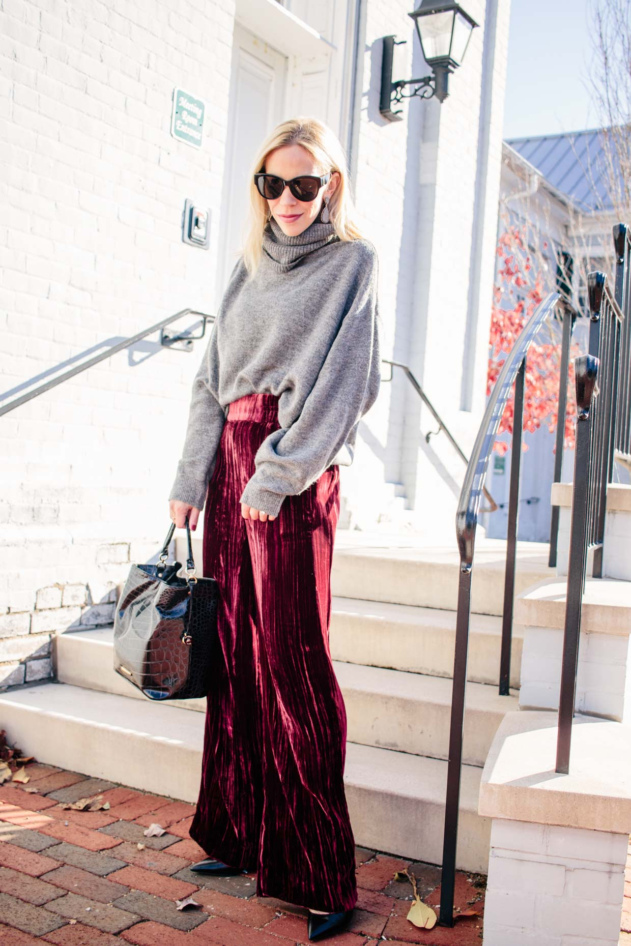 Meagan Brandon Fashion Blogger Of Meagan S Moda Wears Gray Oversized Turtleneck Sweater With Red Velvet Pants For Chic Cozy Holiday Outfit Meagan S Moda