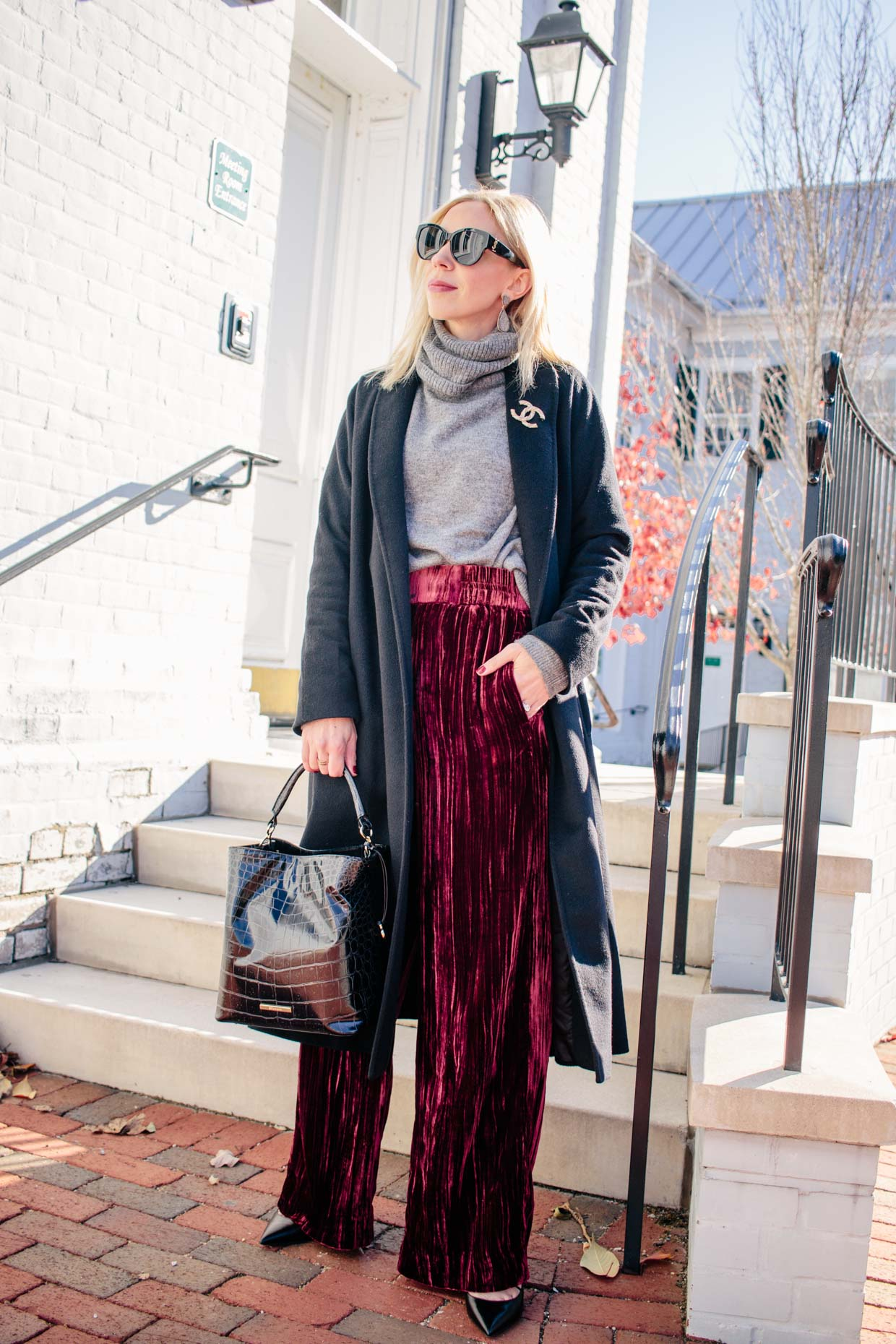 Meagan Brandon Fashion Blogger Of Meagan S Moda Wears Red Velvet Pants With Gray Sweater And Long Black Coat For Holiday Outfit Idea Meagan S Moda